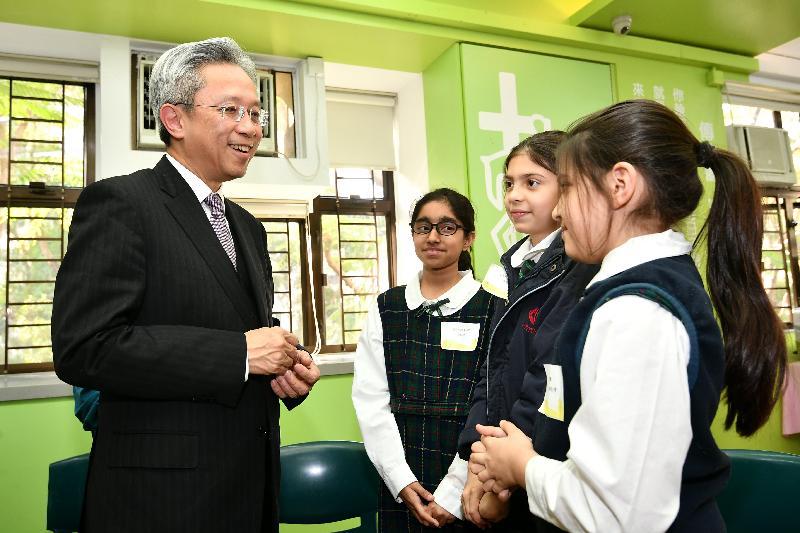 公務員事務局局長羅智光今日(二月二十七日)到訪葵青區。圖示羅智光(左)在循道衛理亞斯理社會服務處與非華裔學生交談,了解他們的學習情況。