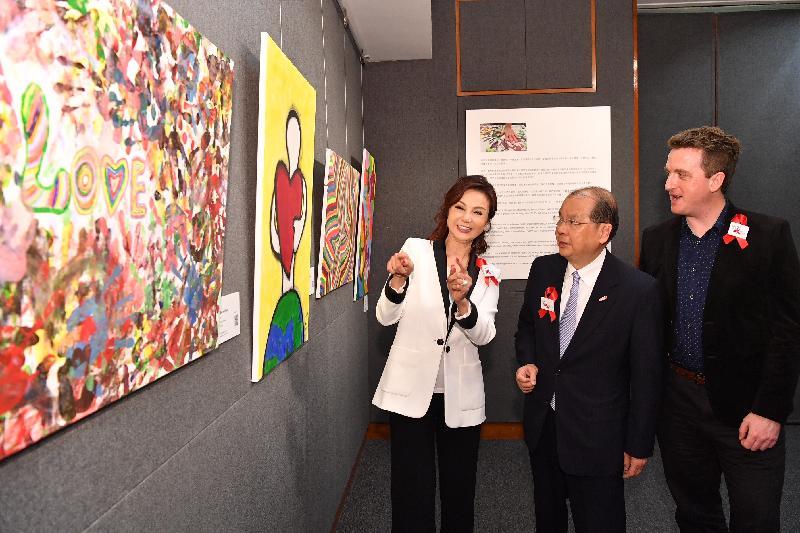 政務司司長張建宗(中)今日(三月五日)參觀「關懷愛滋」舉辦的兼愛並融藝術作品展,並與「關懷愛滋」行政總監齊治之(右)和活動榮譽嘉賓謝玲玲(左)欣賞愛滋病患者的畫作。