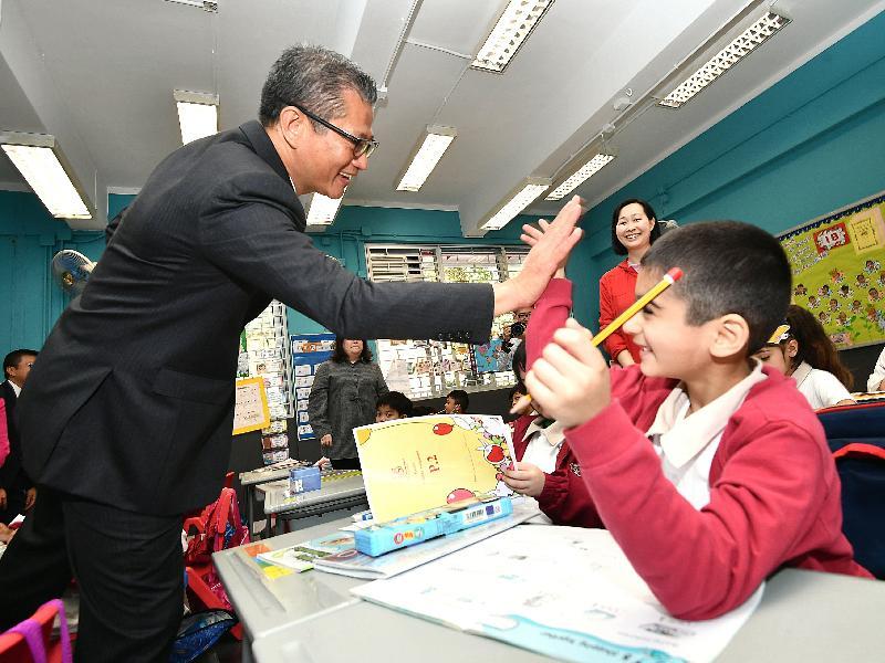 財政司司長陳茂波今日(三月二十八日)到訪李陞大坑學校。圖示陳茂波與該校學生交流。
