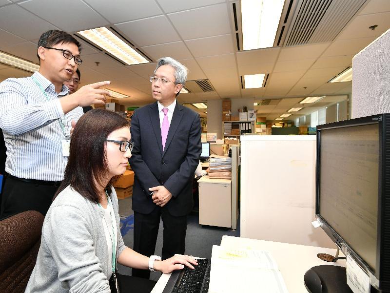 公務員事務局局長羅智光今日(四月十一日)到訪在職家庭及學生資助事務處。圖示羅智光(右一)聽取資助課程學生資助組的同事簡介他們的工作。