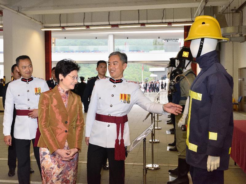 行政長官林鄭月娥今日(五月九日)在消防及救護學院出席香港消防處150周年大會操。圖示林鄭月娥(左)聽取消防處處長李建日(右)介紹不同年代的消防制服。