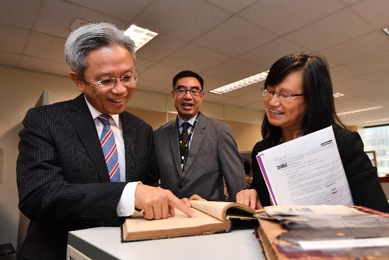 公務員事務局局長羅智光今日(五月十八日)到訪庫務署。圖示羅智光(左一)瀏覽在上世紀初用作記錄領取退休金人士資料的冊子。