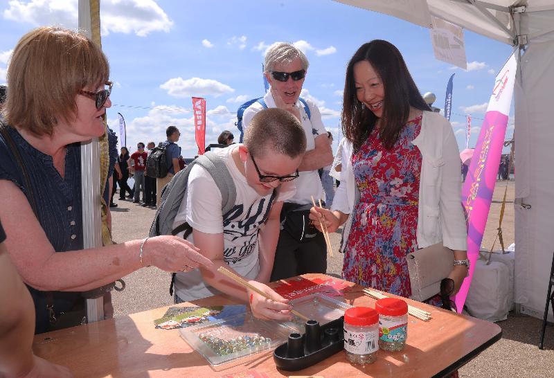 2018倫敦香港龍舟同樂日六月三日(倫敦時間)在倫敦船塢區舉行。圖示香港駐倫敦經濟貿易辦事處(倫敦經貿辦)處長杜潔麗(右)在倫敦經貿辦攤位與公眾一起參與以香港為主題的遊戲。