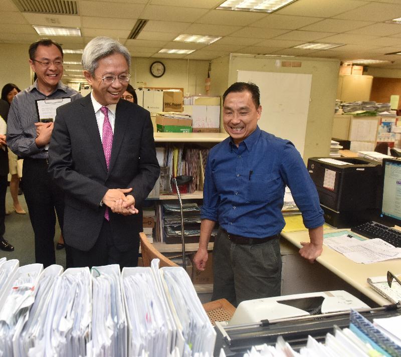 公務員事務局局長羅智光今日(六月六日)到訪民政事務總署。圖示羅智光(中)與灣仔民政事務處一名文書職系同事交流,了解他的日常工作。