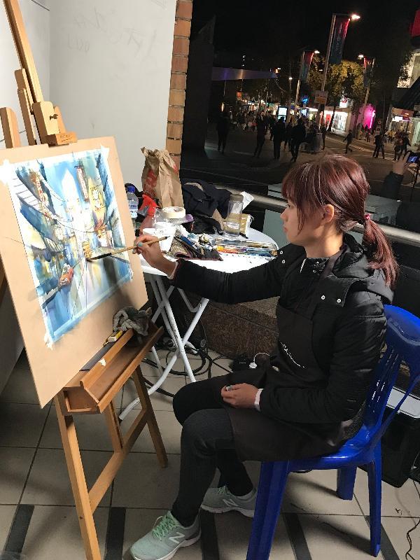 在香港駐悉尼經濟貿易辦事處(經貿處)的支持下,香港年輕水彩畫家趙綺婷在澳洲悉尼車士活區現場繪畫未來城市和空間,為參與「繽紛悉尼燈光音樂節」活動的觀眾帶來驚喜。圖示趙綺婷在車士活區現場繪畫。