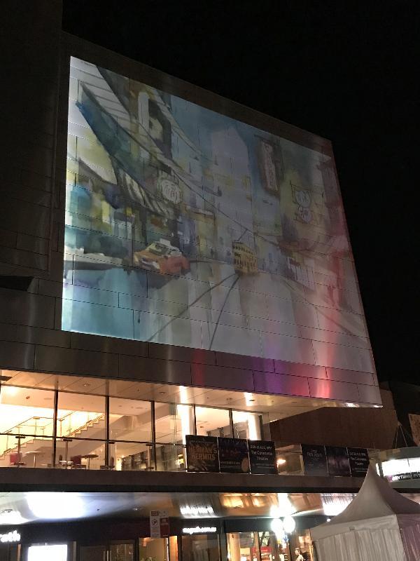在香港駐悉尼經濟貿易辦事處(經貿處)的支持下,香港年輕水彩畫家趙綺婷在澳洲悉尼車士活區現場繪畫未來城市和空間,為參與「繽紛悉尼燈光音樂節」活動的觀眾帶來驚喜。圖示趙綺婷現場繪畫的水彩畫即時投影到車士活大劇院的外牆上。