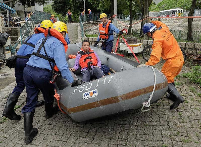 離島民政事務處今日(六月十五日)在大澳舉行跨部門水浸模擬救援及疏散演練。圖示消防員在演練中拯救被困居民。