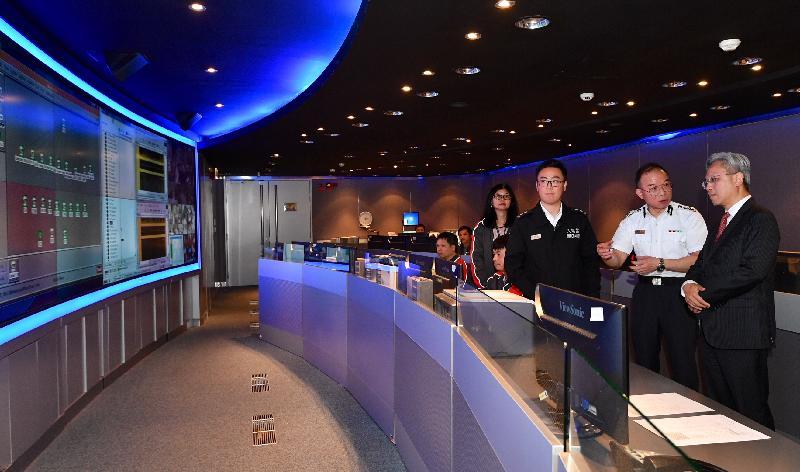 公務員事務局局長羅智光今日(六月二十七日)到訪入境事務處。圖示羅智光(右一)聽取入境處處長曾國衞(右二)講解部門如何透過企業系統管理中心監察所有電腦系統的運作,靈活調配前線人手。