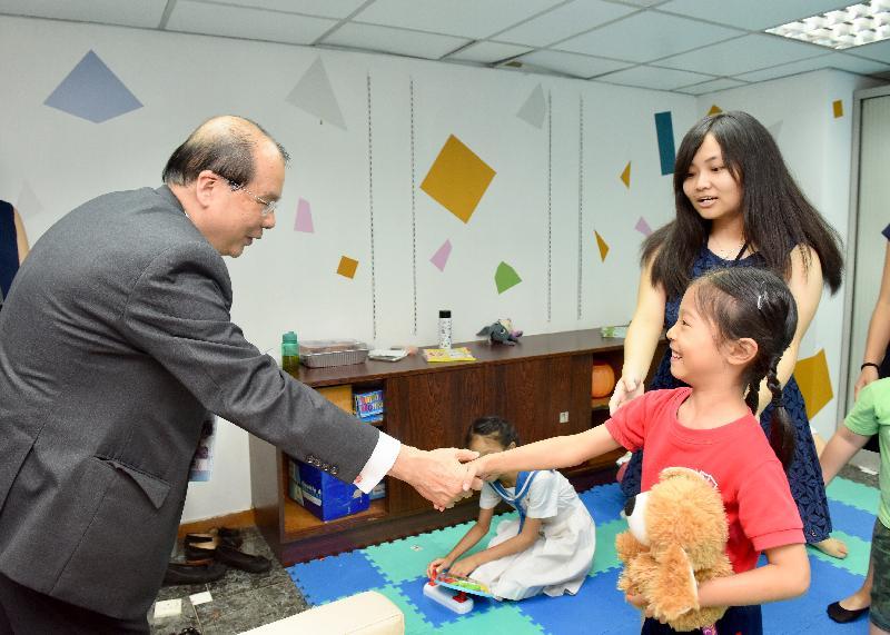 政務司司長張建宗今日(六月二十九日)出席合廠・開幕典禮。圖示張建宗(左一)在「合廠」的兒童遊戲室與一名母親在「合廠」工作的兒童握手。