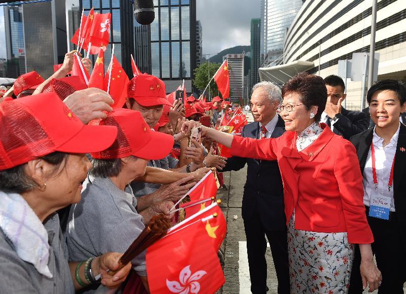 行政長官林鄭月娥(右二)今早(七月一日)在灣仔金紫荊廣場出席香港特別行政區成立二十一周年升旗儀式前與市民握手。旁為其丈夫林兆波博士(右三)。