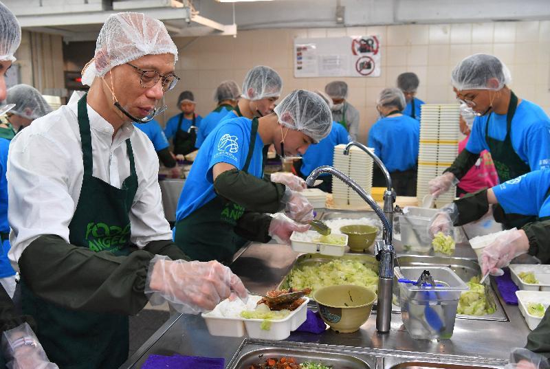 環境局局長黃錦星(左一)今日(七月十六日)到訪惜食堂,與青年義工一同製作免費派發予長者及低收入家庭的飯盒。