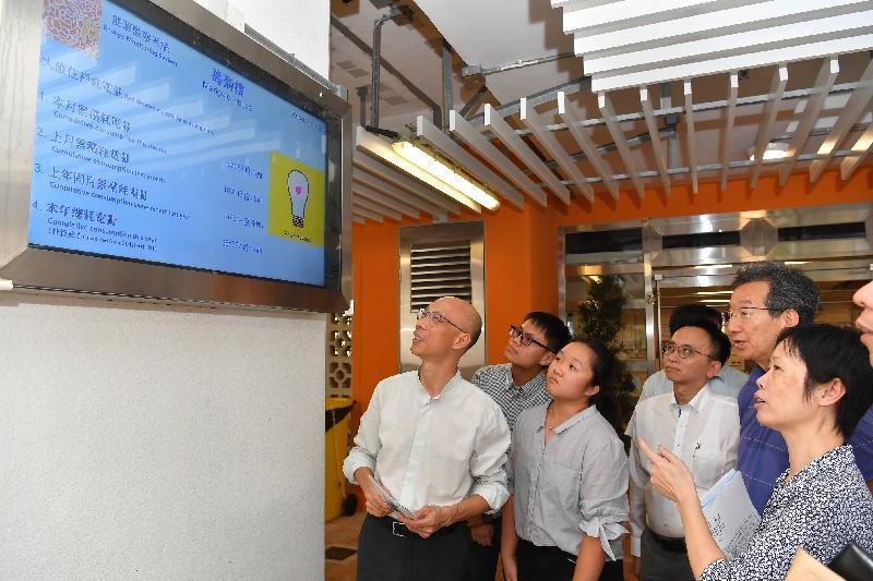 環境局局長黃錦星(左一)今日(七月十六日)參觀設於蘇屋邨壽菊樓入口大堂的能源監察系統。