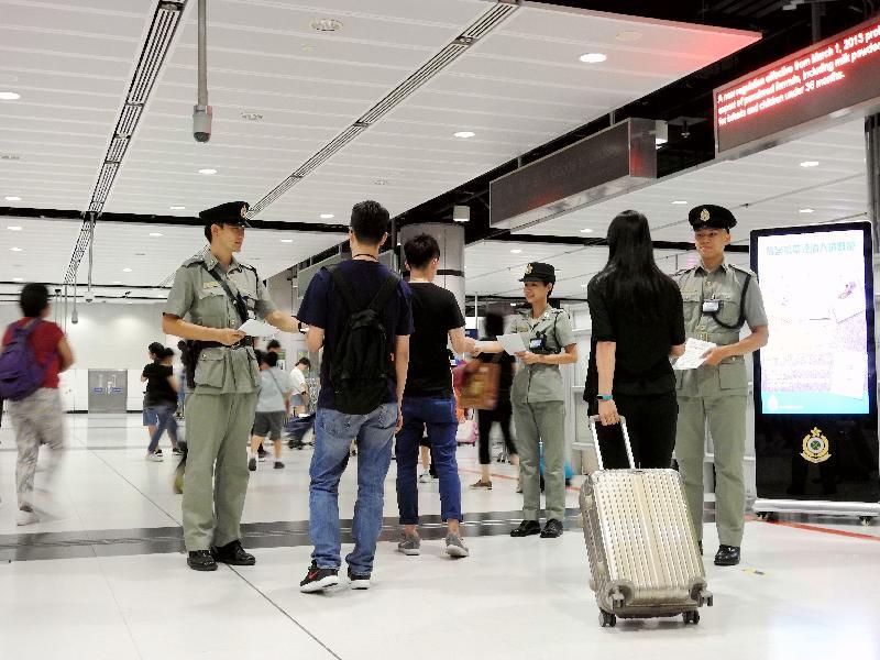 海關人員於暑假期間在邊境管制站派發傳單,提醒旅客切勿攜帶禁運或受管制物品進出香港。