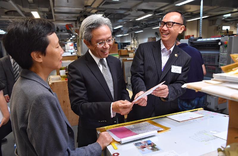 公務員事務局局長羅智光今日(八月二十日)到訪政府物流服務署。圖示羅智光(中)在印務科印刷小組了解由五色柯式印刷機印製的邀請咭的品質。旁為政府物流服務署署長周淑貞(左)。