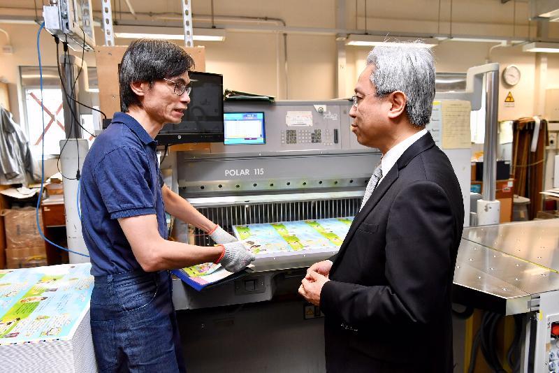 公務員事務局局長羅智光今日(八月二十日)到訪政府物流服務署。圖示羅智光(右)向印務科裝訂小組的同事了解切紙機的操作。