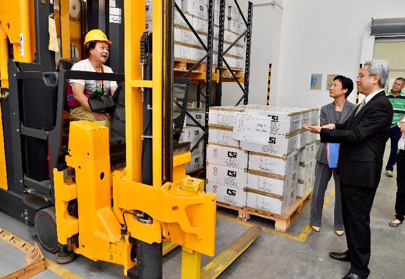 公務員事務局局長羅智光今日(八月二十日)到訪政府物流服務署。圖示羅智光(右一)參觀物料供應管理科儲存及分發組常備庫存物料倉時,觀看同事操作高層揀選車提取貨物。
