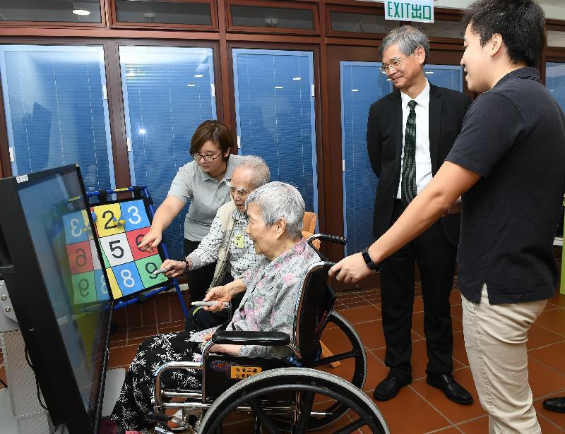 勞工及福利局局長羅致光博士今日(八月二十八日)中午到訪志蓮護理安老院和志蓮日間護理中心探訪長者。圖示羅致光博士(右二)觀看長者進行認知能力訓練,延緩退化。