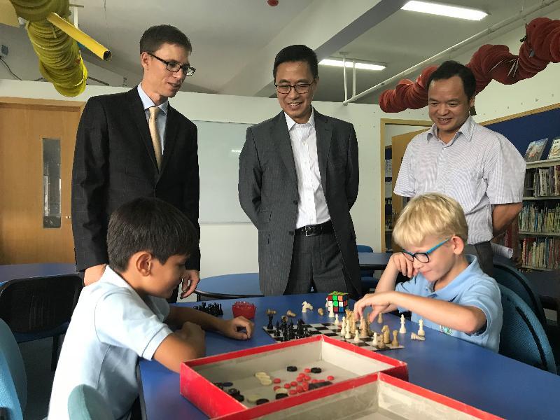教育局局長楊潤雄今日(八月二十九日)到廣東省珠海及中山訪問。圖示楊潤雄(中)和珠海市教育局局長林日團(右)在參觀珠海國際學校的圖書館時,觀看兩名學生下棋。