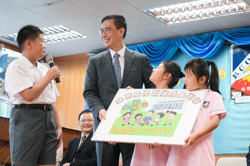 教育局局長楊潤雄(左二)今日(九月三日)在英皇書院同學會小學第二校開學禮上獲同學送贈一幅畫作。
