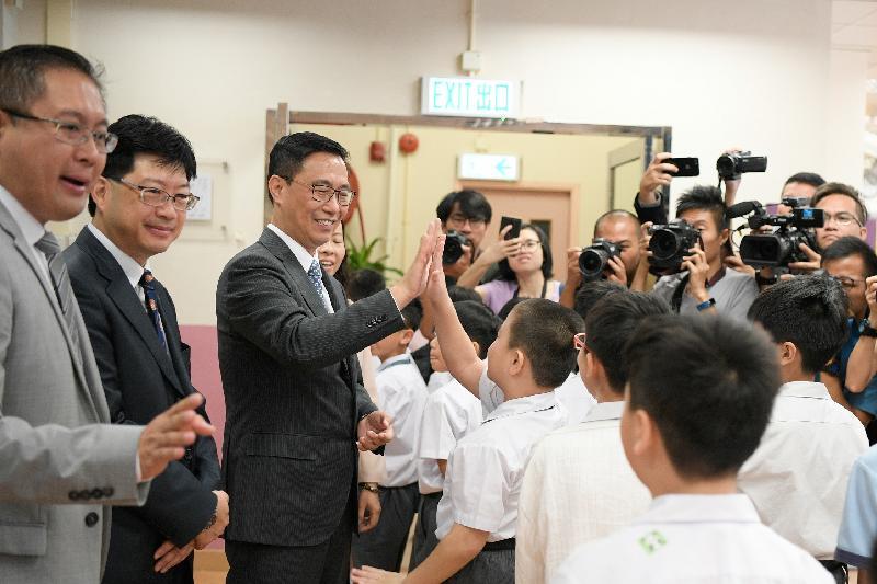教育局局長楊潤雄(左三)今日(九月三日)在英皇書院同學會小學第二校開學禮上與學生問好。