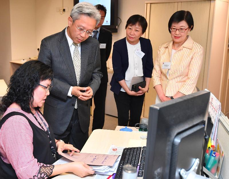 公務員事務局局長羅智光今日(十月二日)到訪衞生署衞生防護中心。圖示羅智光(左二)聽取中央呈報辦公室同事介紹他們如何透過通報機制所收集的信息,監察香港的傳染病。