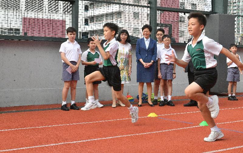 行政長官林鄭月娥今日(十月十二日)下午到訪位於深水埗的英華小學。圖示林鄭月娥(後排左四)觀看學生參加田徑練習。