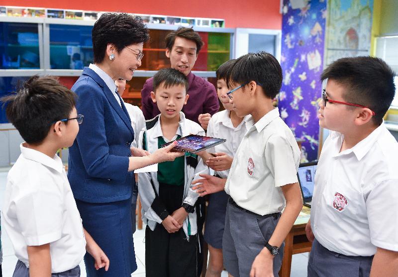 行政長官林鄭月娥今日(十月十二日)下午到訪位於深水埗的英華小學。圖示林鄭月娥(左二)與參加視藝進階班的同學交談。