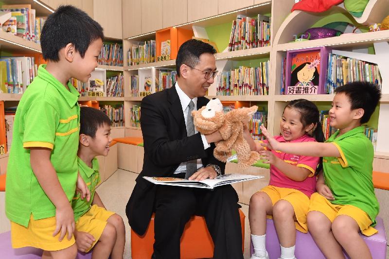 教育局局長楊潤雄(中)今日(十月十八日)在探訪東華三院田灣(一九九六至一九九七總理)幼稚園期間,參與學童的閱讀活動。