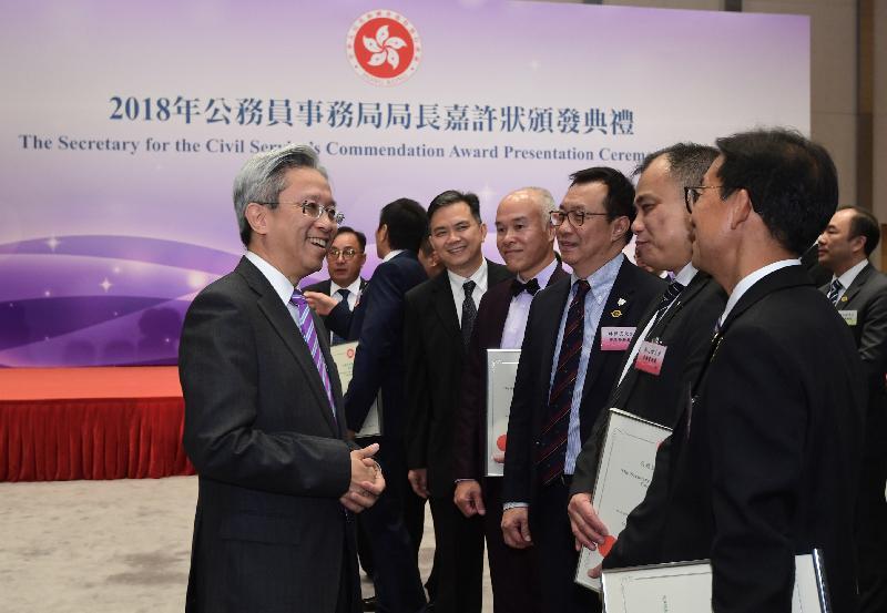 公務員事務局局長羅智光(左一)今日(十月二十三日)在公務員事務局局長嘉許狀頒發典禮上祝賀和讚揚獲獎的公務員。
