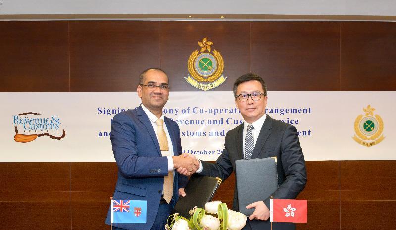 香港海關關長鄧以海(右)與斐濟稅務與海關署署長Visvanath Das(左)今日(十月二十四日)在香港海關總部大樓簽訂《海關互助合作安排》。圖示雙方交換文本。