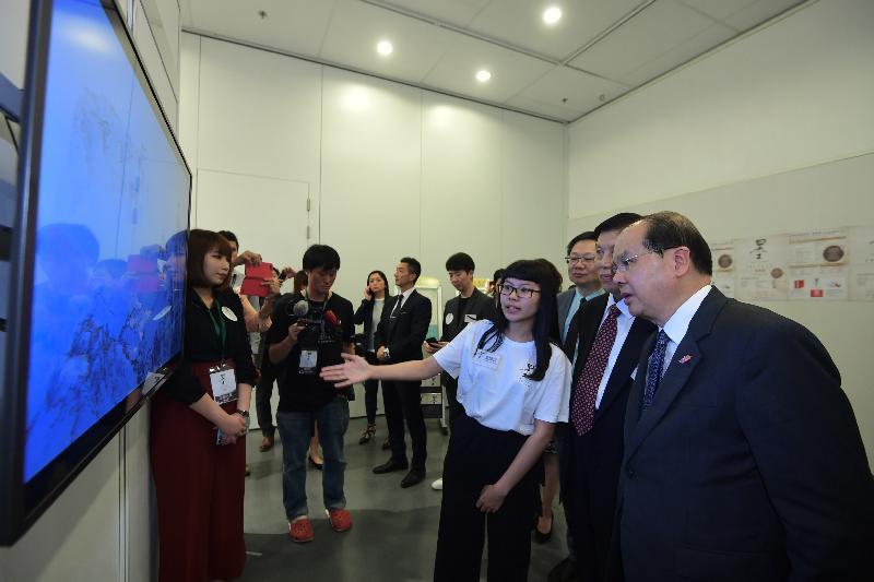 署理行政長官張建宗今日(十月二十四日)出席「全球水墨畫大展──教育篇」。圖示張建宗(右)聽取工作人員介紹展覽,