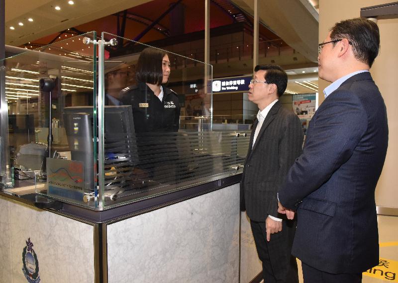 保安局局長李家超(中)今日(十月二十四日)到訪港珠澳大橋的香港口岸。圖示李家超在旅檢大樓視察入境事務處人員為旅客進行出入境程序。