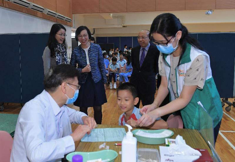 食物及衞生局局長陳肇始教授(後排中)今日(十一月五日)上午於「學校外展疫苗接種先導計劃」的外展疫苗接種活動上,陪同學童接種疫苗。