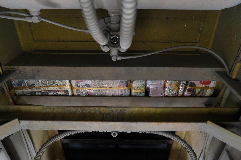 香港海關昨日(十一月十三日)在落馬洲管制站一輛出境貨櫃車上檢獲三百三十部懷疑走私智能電話,估計市值約五十萬元。圖示車底的暗格。