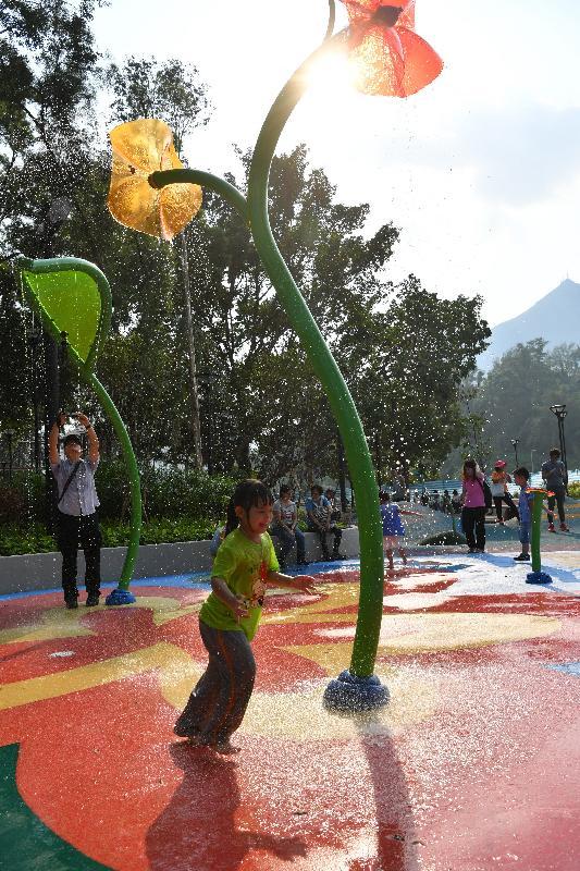 屯门公园共融游乐场十二月三日启用,是本港首个把「水」和「沙」两项自然元素纳入设计的无障碍儿童游乐空间。图示场内的「光影荷花」区域,设有花型的高空洒水装置,儿童可尽情享受在公园嬉水的乐趣。