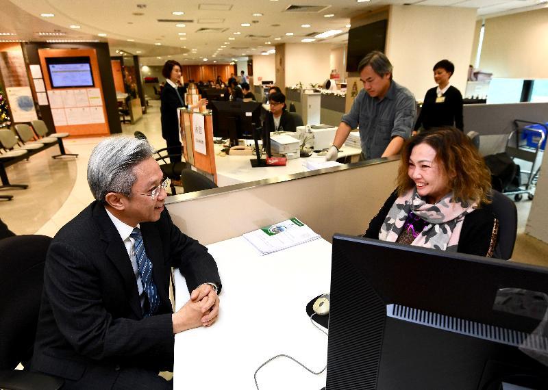 公務員事務局局長羅智光今日(十二月十四日)到訪土地註冊處。圖示羅智光(左一)在客戶服務中心與前線同事交談,了解她的工作。