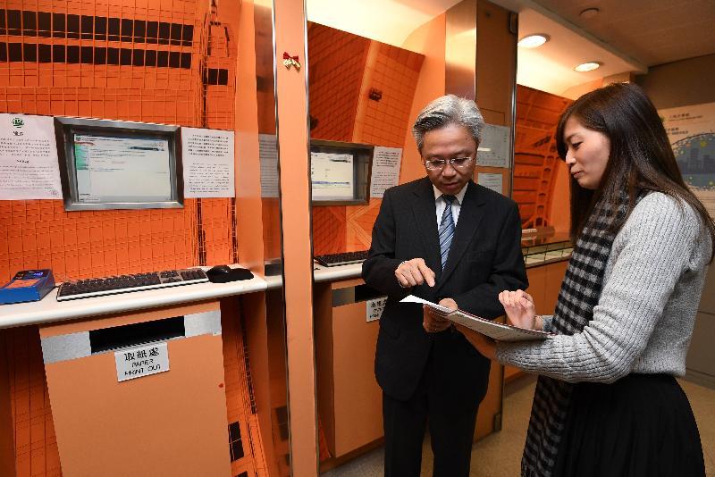 公務員事務局局長羅智光今日(十二月十四日)到訪土地註冊處。圖示羅智光(左)聽取同事簡介「綜合註冊資訊系統」的網上土地紀錄查閱服務。