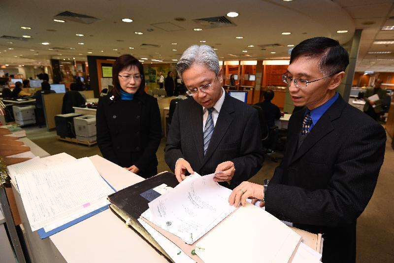 公務員事務局局長羅智光今日(十二月十四日)到訪土地註冊處。圖示羅智光(中)瀏覽存放於客戶服務中心的業主立案法團登記紀錄。旁為土地註冊處處長張美珠(左)。
