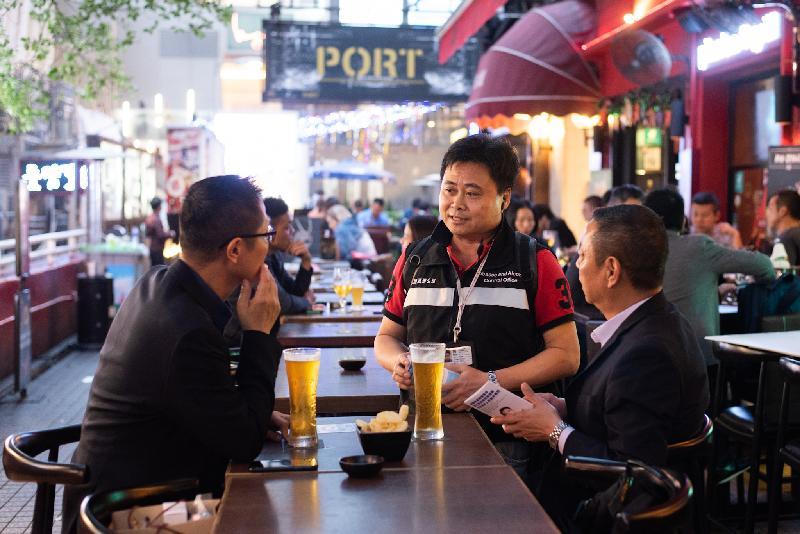 衞生署控煙酒辦公室今日(十二月二十一日)表示,將在聖誕新年期間加強巡查和執法行動,以防止向未成年人士售賣酒類飲品,並遏止酒吧內違例吸煙的情況。圖示控煙酒督察在尖沙咀諾士佛臺向酒吧顧客派發傳單,提醒市民遵守法例,不要在禁止吸煙區吸煙。