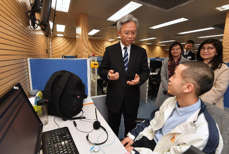 公務員事務局局長羅智光今日(一月十日)到訪效率促進辦公室。圖示羅智光(左一)在1823中心與一名傷健同事交談,了解部門協助他融入工作環境的支援。旁為效率專員聶世蘭(右一)。