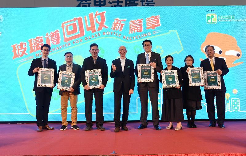 環境局局長黃錦星(左四)今日(一月十日)在《玻璃樽回收新篇章》啟動禮致送感謝狀予曾推行自願性玻璃回收計劃的機構代表。