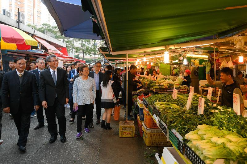 財政司司長陳茂波(前排左二)今日(一月十一日)下午到訪東區,並在東區區議會主席黃建彬(前排左一)和東區民政事務專員陳尚文(第二排左一)陪同下參觀排檔區攤檔,與商戶交流。