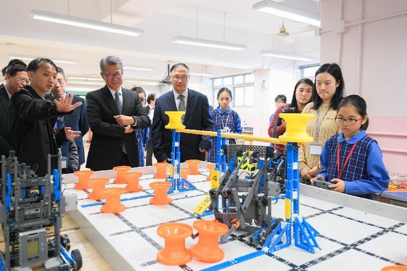 財政司司長陳茂波今日(一月十一日)下午到訪東區愛秩序灣官立小學。圖示陳茂波(左四)參觀校內與STEM(科學、科技、工程和數學)相關的教育項目。