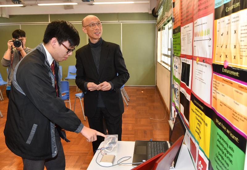环境局局长黄锦星(右)今日(一月二十一日)到访九龙城区一所中学,了解学生在环保方面的研究项目。