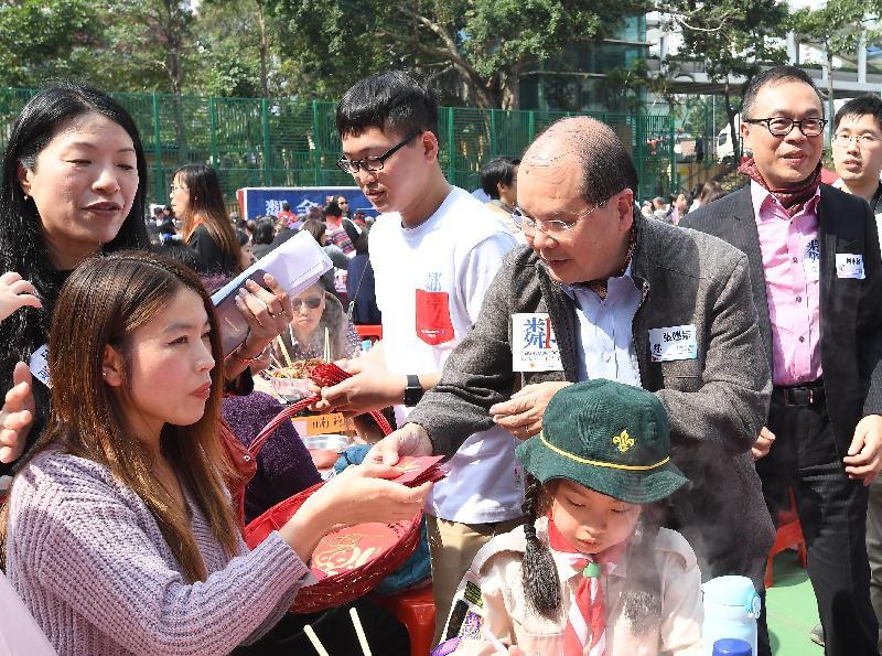 政務司司長張建宗今日(一月二十六日)出席香港青年協會舉辦的二○一九年鄰舍團年飯。圖示張建宗(右二)向參加者派發利是。