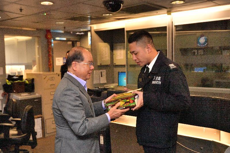 政务司司长张建宗(左)今早(二月五日)到访落马洲管制站。图示张建宗向当值人员派发糖果,感谢所有当值人员在新春期间紧守岗位,为市民提供优质服务。
