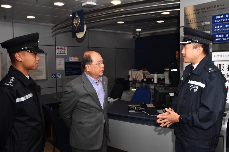 政務司司長張建宗(中)今早(二月五日)到訪警務處位於落馬洲管制站的報案中心,聽取香港警務處落馬洲分區指揮官張國威(右)講解警務人員農曆新年期間在管制站的工作。