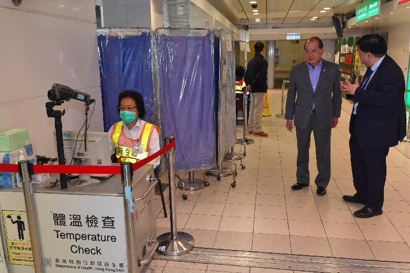 政务司司长张建宗(右二)今早(二月五日)到访落马洲管制站,并在卫生署总港口卫生主任何理明医生(右一)陪同下了解管制站卫生署人员的工作。