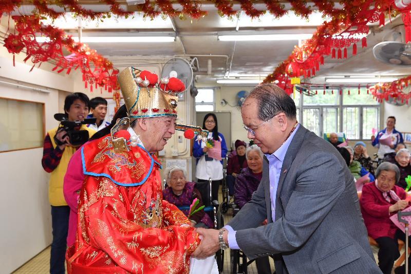 政务司司长张建宗(右)今早(二月五日)到访大埔一所护理安老院,与长者共庆新春。图示张建宗向一位装扮成「财神」的长者拜年。