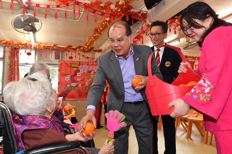 政務司司長張建宗今早(二月五日)到訪大埔一所護理安老院,向長者送上節日祝賀。圖示張建宗(右三)向長者送上甜柑。